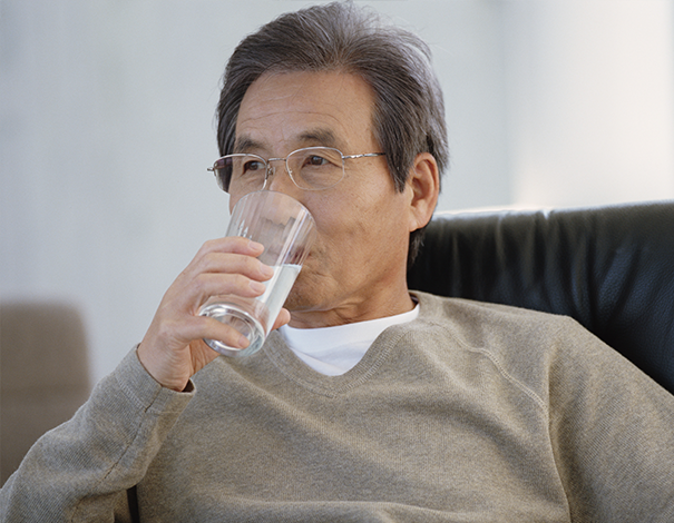 Pensive man drinking a glass of water on couch - Hydration