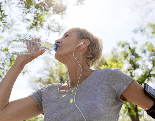 woman drinking water and getting rehydrated after jog