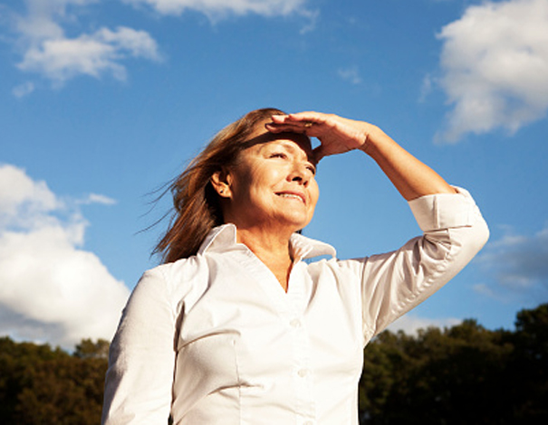 Woman staring out into a field shielding her eyes from the sun