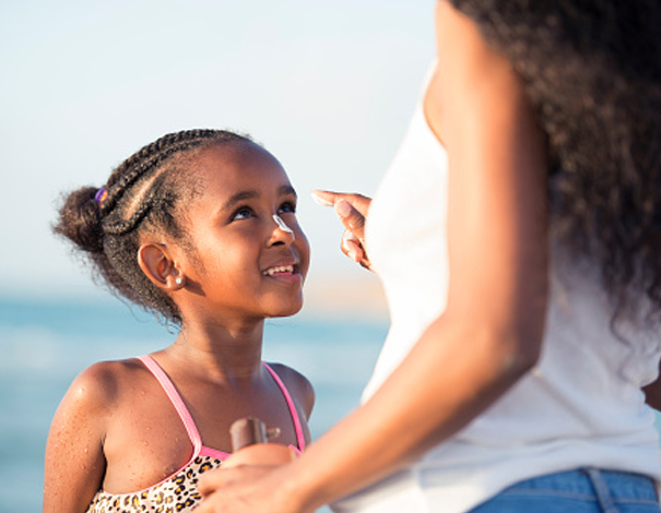 mom putting sunscreen on her daughters face