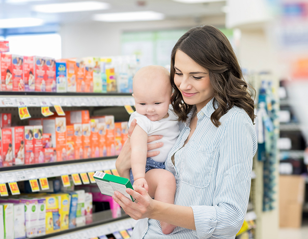 Woman shopping at pharmacy holding product